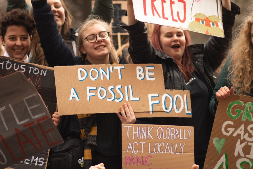 Young climate protesters holding signs/ CC0 Callum Shaw