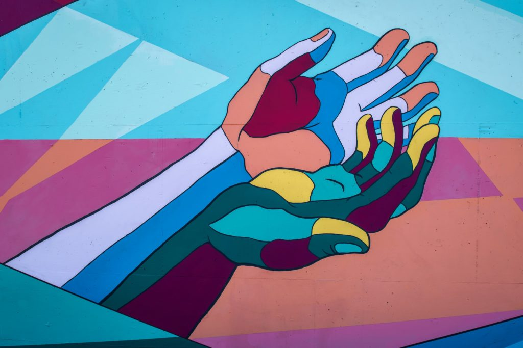 Artwork painting of colourful hands on a wall/ CC0 Tim Mossholder