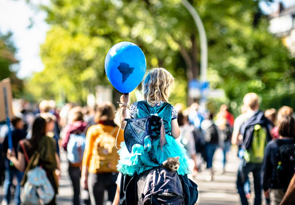 Child holding a balloon during a climate march/ CC0 Mika Baumeister