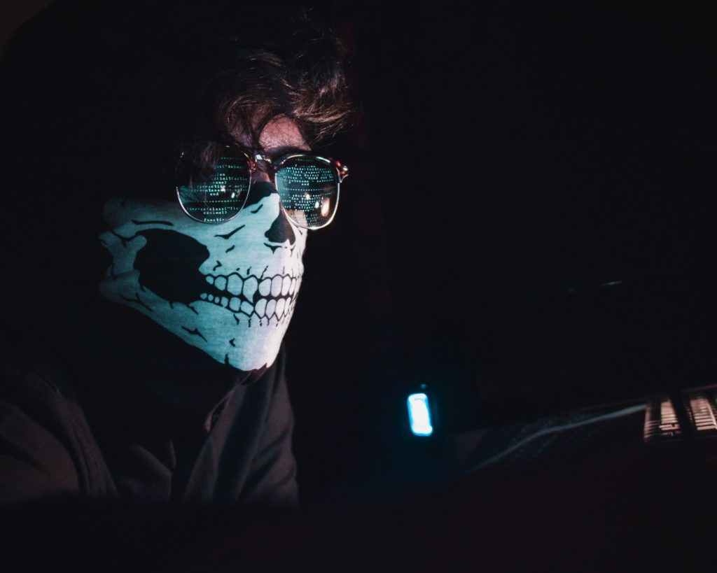Person wearing skull mask in front of computer screen / CC0 nahel-abdul-hadi